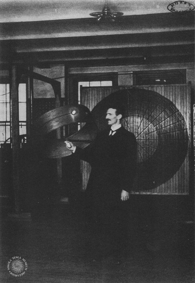 Nikola Tesla holding a helical receiver coil