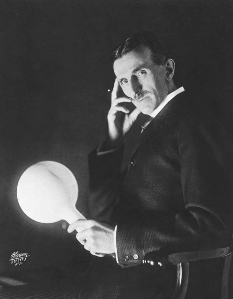 Nikola Tesla holding a wireless light bulb.
